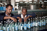 AMBO, ETHIOPIA - NOVEMBER 15: A woman checks bottles of mineral rich sparkling water as it is made in this factory who was established 80 years ago in Sekele locality near a hot spring 130 km west of Addis Ababa on November 15, 2010 in AMBO, Ethiopia.The brand has about 85 percent of the market in the country. Recently new investments were made by the company and SAB Miller of 21 million USD. New products which are in the pipeline are called Ambo Plus, and they are orange- apple- pineapple- and lemon flavored Ambo water. (Photo by Per-Anders Pettersson)
