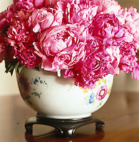 Detail of a china vase filled with brilliant pink peonies