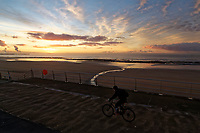 A man cycles by the sea front during an early frosty morning in Swansea, Wales, UK. Tuesday 12 December 2017