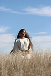 A young Native American Indian Woman looking into the sun while standing in the grasses of  South Dakota