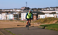 A man rides his bike on the cucle path enjoy in Swansea Bay, Wales, UK. Friday 27 October 2017