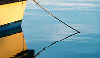 A reflection of a mooring line and the bow of a boat in the calm waters of Kaneohe Bay, O'ahu.