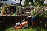 Switzerland. Canton Ticino. Tenero. Camping Campofelice. Tullio Bruno is 64 years old and has been working as a gardener for the last 39 years in the campsite. He is cutting the grass with an electric battery powered lawnmower by STIHL. The mower is quiet, powerful, gives a stunning cut and is cordless.  A campervan (or camper van), sometimes referred to as a camper, or a caravanette, is a self-propelled vehicle that provides both transport and sleeping accommodation. A motorhome (or motor coach is a type of self-propelled recreational vehicle (RV) which offers living accommodation combined with a vehicle engine. Motorhomes are part of the much larger associated group of mobile homes which includes caravans, also known as tourers, and static caravans. A caravan, travel trailer, camper or camper trailer is towed behind a road vehicle to provide a place to sleep which is more comfortable and protected than a tent. It provides the means for people to have their own home on a journey or a vacation. Campers are restricted to designated sites for which fees are payable. The flag of Switzerland consists of a red flag with a white cross (a bold, equilateral cross) in the centre. It is one of only two square sovereign-state flags. 20.07.2018 © 2018 Didier Ruef