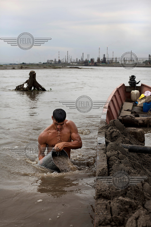 A man mines sand which is used in construction from the bed of the Magdalena River. /Felix Features