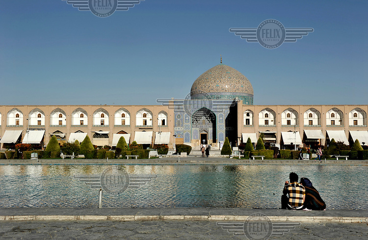 A young couple sit togather in the Naghsh E Jahan Square.