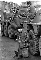 Major Chris Miers, the British Army's official war artist, at work in Belfast,  during the N Ireland Troubles. Whilst be sketches a bodyguard remains vigilant. Major Miers is serving with the Royal Green Jackets. 197211200731e.<br />