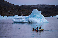 Kayakers in inflatable kayak paddling through icebergs in Kong Oscars Havn, Tasiilaq, Greenland