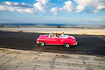 HAVANA, CUBA - JANUARY 1: A vintage car drives along the Malecon in Havana, Cuba on January 1, 2014.  Prior to 2011, Cuban citizens could only purchase pre-revolution vehicles.