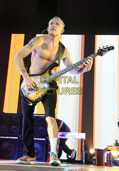 Michael 'Flea' Balzary.The Red Hot Chili Peppers made a stop on their tour at the Gwinnett Arena in Duluth, GA, where they played to a packed venue of enthusiastic fans, Duluth, GA., USA..April 10th, 2012.RHCP on stage in concert live gig performance performing music full length topless chest tattoos bass guitar black trousers short leg cut ripped socks pink trainers sneakers .CAP/ADM/DH.©Dan Harr/AdMedia/Capital Pictures.