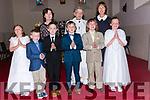 Pupils from Scoil Mhaolchéadair Caroline Ní Dhúbhda, Shane Bacaéir, Darragh Ruiséal, Dónal Ó Laighin and Ríona Bacaéir, and pupil from Scoil Naomh Eirc Ruairí Ó hUanachain, the day of their First Communion, pictured with múinteoir Mai Bn Uí Bhruic, múinteoir Aine de Londra, and an tAthair Hickey at Carrig Church on Saturday noon.