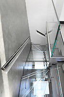 Triangular niches have been carved into the concrete walls of the stairwell to recess the metal handrails