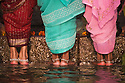 Women in sarees and bracelets around their ankles standing on steps in water of Ganges River;  Varanasi has been a cultural and religious center in northern India for several thousand years, Varanasi, Uttar Pradesh, India