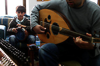 """FOR FAOIROUZ SONG """"THE FLOWER OF THE CITIES"""" - A Palestinian boy plays the Darbuka  and his teacher the Oud during a lesson in the Edward Said National Conservatory of Music in East Jerusalem. Photo by Quique Kierszenbaum."""