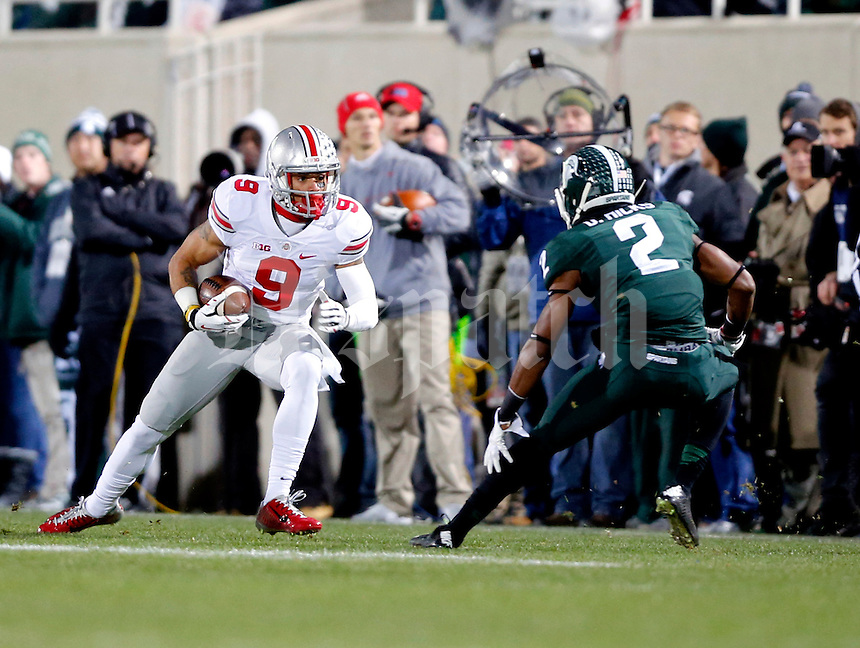 Ohio State Buckeyes wide receiver Devin Smith (9) heads up field after a catch against Michigan State Spartans cornerback Darian Hicks (2) during the 1st quarter at Spartan Stadium in East Lansing, Michigan on November 8, 2014.  (Dispatch photo by Kyle Robertson)