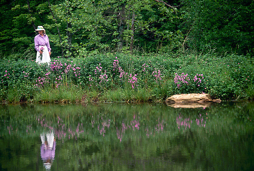 Young woman picks purple flowers from dam across lake