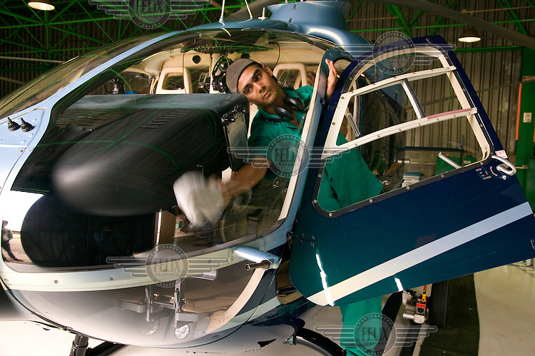 A Helicidade member of staff cleans a helicopter in one of their hangars.