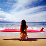 Classic Surfer girl on the beach with surfboard on the island of Maui, Hawaii