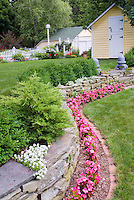Stone wall with pink flowering wax begonias, Iberis atop stone wall, evergreen shrubs, Buxus boxwood, white picket fence, garden shed, bird house, garage, neat brick edging next to lawn grass, steps to tiered two level landscaping, dealing with a slope in the backyard landscape