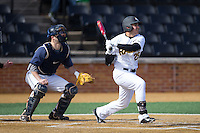 Vimael Machin (25) of the VCU Rams follows through on his swing against the Georgetown Hoyas at Wake Forest Baseball Park on February 13, 2015 in Winston-Salem, North Carolina.  The Rams defeated the Hoyas 6-3.  (Brian Westerholt/Four Seam Images)