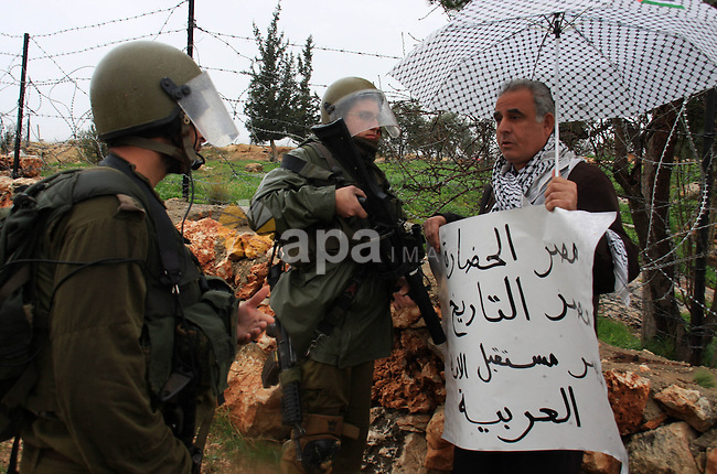 Israeli soldiers stand guards during a protest against Israel's separation barrier in the West Bank village of Bilin near Ramallah, Friday, Feb 4, 2011. Photo by Wagdi Eshtayah