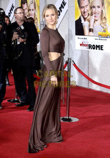 """KRISTEN BELL .Attending the Los Angeles Premiere of """"When In Rome"""" held at The El Capitan Theater, Hollywood, CA, USA, .27th January 2010..arrivals full length brown long maxi dress long sleeves sleeved cut out away sides rope side .CAP/ADM/TC.©T. Conrad/AdMedia/Capital Pictures."""