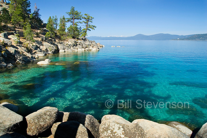 An image of the shoreline of Lake Tahoe and its beautiful blue green water.