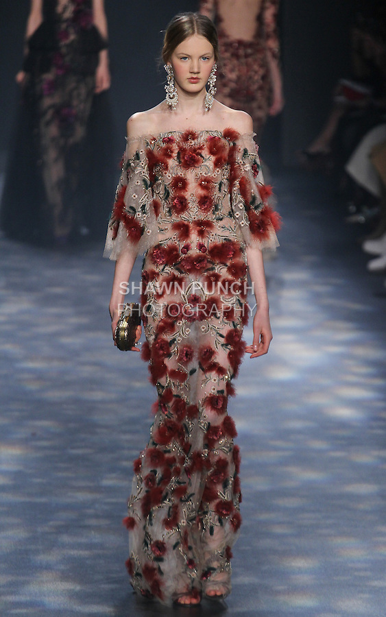 Model Noa walks runway in a nude tulle off-the-shoulder column gown with flutter sleeves with red and gold feather flower embroidery, from the Marchesa Fall 2016 collection by Georgina Chapman and Keren Craig, presented at NYFW: The Shows Fall 2016, during New York Fashion Week Fall 2016.