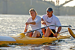 Mature couple rowing outrigger canoe