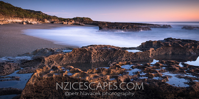 Beach and limestone rocks with water pools on Truman Track in twilight in Punakaiki, Paparoa National Park, West Coast, New Zealand, NZ