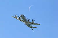 A United States Navy P-3c Orion anti-submarine and maritime surveillance aircraft assigned to VP-30, The Pro's Nest, from Jacksonville NAS flies below the moon's thin crescent.