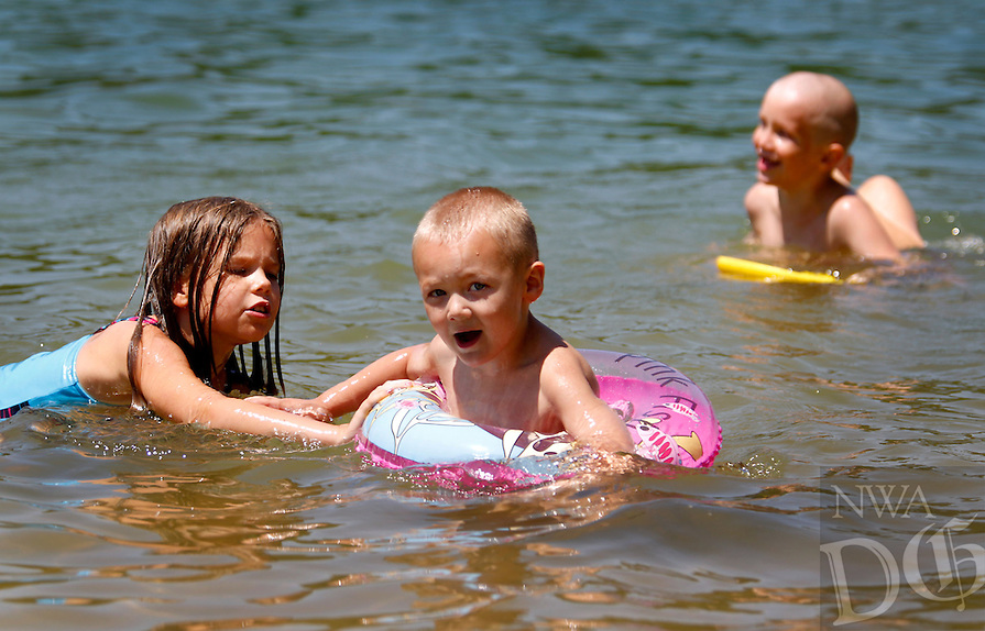 NWA Media/JASON IVESTER --06/20/2014--<br /> Siblings Joclynn (cq) Killbreth (cq) (from left), 9, Tristan Long, 4, Bastein Long, 7, and James Long, 10, play in the swimming area at Rocky Branch Park on Beaver Lake on Friday, June 20, 2014, in Rogers. The children, along with their other siblings, Connor Smith and Sarah Long, were camping at the campground with their parents, Joe and Julie Long, all of Bentonville.