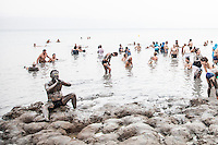 People covered in mud bathing  in the Dead Sea, the waters of which are renowned for its health benefits.