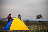 Pictured: Two women at the Idomeni camp Monday 29 February 2016<br /> Re: A crowd of migrants has burst through a barbed-wire fence on the FYRO Macedonia-Greece border using a steel pole as a battering ram.<br /> TV footage showed migrants pushing against the fence at Idomeni, ripping away barbed wire, as FYRO Macedonian police let off tear gas to force them away.<br /> A section of fence was smashed open with the battering ram. It is not clear how many migrants got through.<br /> Many of those trying to reach northern Europe are Syrian and Iraqi refugees.<br /> About 6,500 people are stuck on the Greek side of the border, as FYRO Macedonia is letting very few in. Many have been camping in squalid conditions for a week or more, with little food or medical help.
