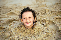 Delighted young girl buried in the beach sand.