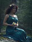 Artistic romantic portrait of a beautiful young woman in a green summer boho dress sitting in the nature with a wild flower in her hands and a wreath made of dry tree branches on her head