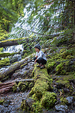 USA, Oregon, Oregon Cascades, a young boy hikes and checks out the upper Proxy Falls in the Wilamette National Forest in the early Fall, McKenzie Pass