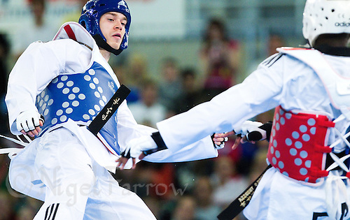 05 MAY 2012 - MANCHESTER, GBR - Aaron Cook (GBR) of Great Britain (left) looks for an opening to attack Ynoussa Sawadogo of France during their men's 2012 European Taekwondo Championships -80kg category second round match at Sportcity in Manchester, Great Britain (PHOTO (C) 2012 NIGEL FARROW)