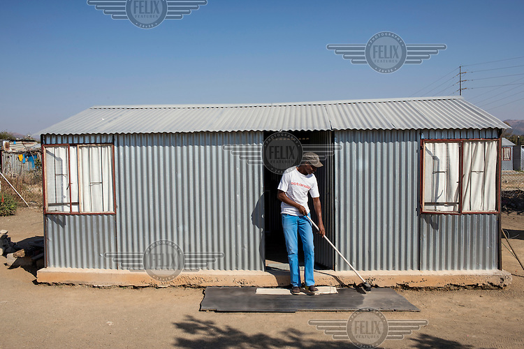 Alex, 32, a community leader, sweeps the entrance to his home.