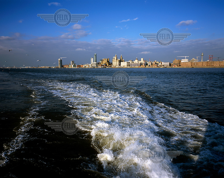 Looking back at the city of Liverpool from the back of a ferry on the River Mersey with view of the harbour and the skyline of the city with the Royal Liver Building, Cunard Building and Port of Liverpool Building.