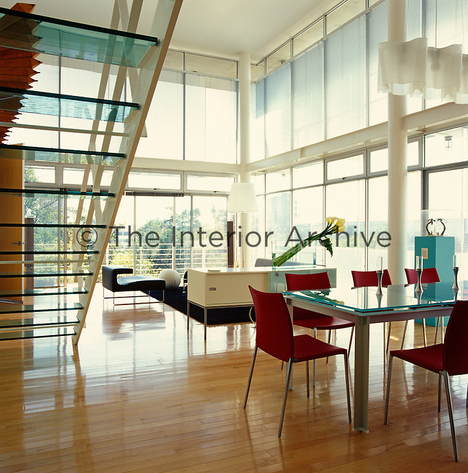 The double-height living/dining area is surrounded on all sides by floor to ceiling windows