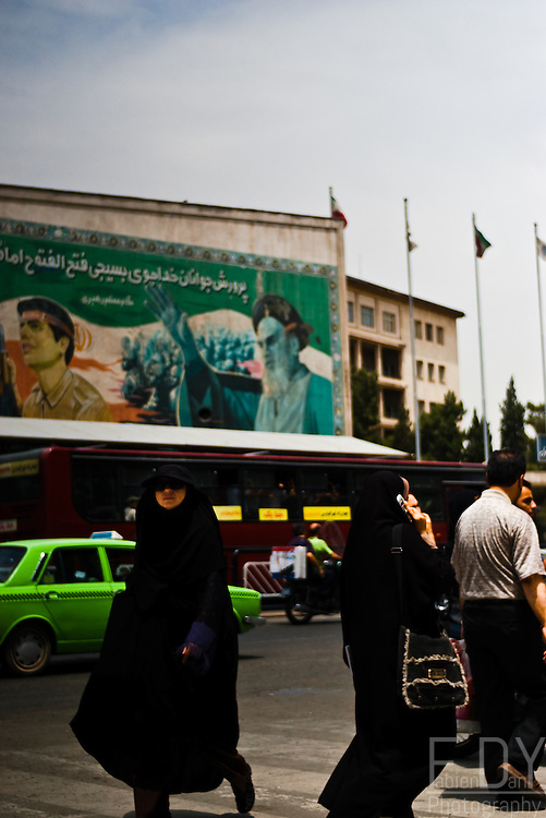 Chador-clad women walking past on of Tehran University's faculties, on Enghelab street, under one of the many mural paintings depainting Ayatollah Khomeini