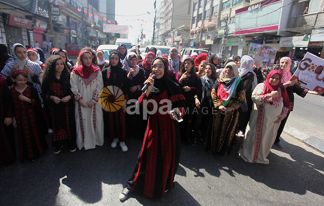 Palestinian girls wear traditional dress as they take part in a rally marking the Palestinian traditional customs day, in Gaza City, on July 30, 2019. Photo by Mahmoud Ajjour