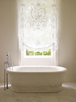 A lace curtain softens the light from the sash window in this marble bathroom