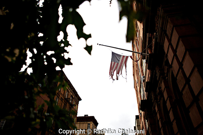 NEW YORK-NOVEMBER 02: An American flag destroyed by Hurricane Sandy flies from the front of a building on Hester Street  November 2, 2012. The downtown area remained without electricity as recovery efforts continued.