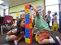 NWA Democrat-Gazette/BEN GOFF &bull; @NWABENGOFF<br /> Katelyn Nguyen (from left) Binnson Ross and William Van Hersh, all 5, construct a castle for their toy dinosaurs on Monday Aug. 3, 2015 in Natalie Marts' Kindergarten class during the first day of school at R.E. Baker Elementary in Bentonville. Baker and Elm Tree elementary schools in Bentonville run on a nontraditional calendar.