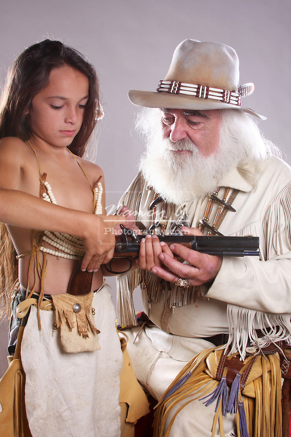 A mountain man teaching a young Native American Indian boy about shooting a revolver