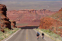 Cyclists Warren Moe and Susan DeLisle, left, and guide Eric Proano, decsend teh cut through the Comb Ridge uplift bewteen Blff and Mexican Hat, Utah, July 1, 2010. The Red Rock Canyons Tour, organized by Lizard Head Cycling Tours, wound through 400 miles of the desert southwest. The route traveled through canyons and national monuments in Colorado, Utah and Arizona, ending at Lake Powell. (Kevin Moloney for the New York Times)