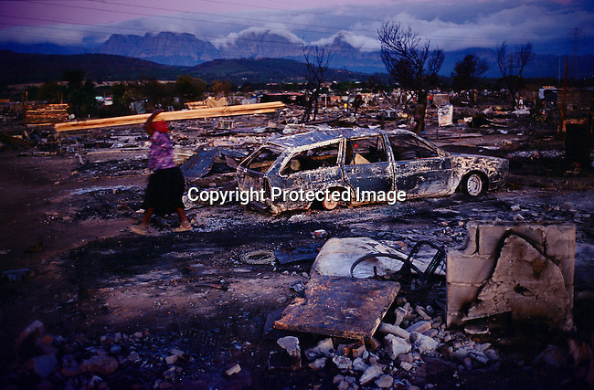 A woman walks past a burned out car and shacks, in a poor township, in Strand, Cape Town, South Africa. A fire burned down about 300 shacks a day earlier and about 1,500 people became homeless. (Photo by: Per-Anders Pettersson)
