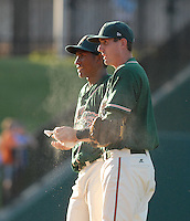 Third baseman Chase Austin (8) of the Greensboro Grasshoppers, right, talks with starting pitcher Natividad Dilone (38) on the mound in a game against the Greenville Drive on June 14, 2010, at Fluor Field at the West End in Greenville, S.C. Photo by: Tom Priddy/Four Seam Images