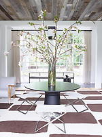 The living area is both dramatic and relaxed with just the right contrast between the classic architecture and the minimalist furnishings. The lofty ceiling is clad in ravaged barn siding and the floor is laid with wide-plank oak overlaid with a graphic rug by Joseph Carini Carpets. An arrangement of blossom stands on a pedestal table and in the background is a bench is by Lucca & Co.